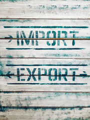 Import / Export inscription painted on wooden background