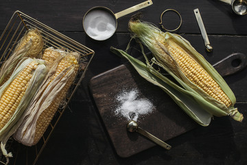 Grains of ripe corn on dark wooden background with cutting board and salt. Summer vegan dinner or snack. Flat lay top view