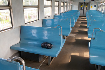 the black package lies in the empty passenger train on a seat. package of unknown contents