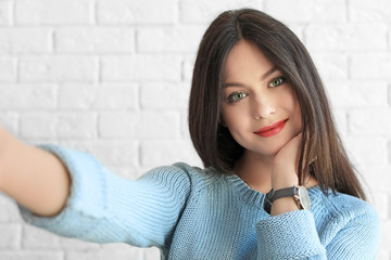 Attractive young woman taking selfie near brick wall