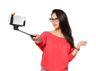 Attractive young woman taking selfie on white background