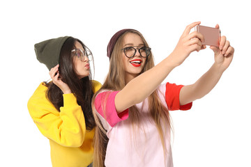 Attractive young women taking selfie on white background