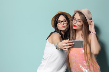 Attractive young women taking selfie on color background