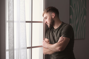 Depressed young man near window at home