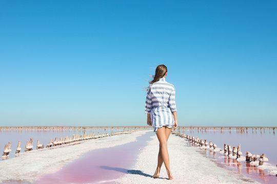 Beautiful woman posing near pink lake on summer day