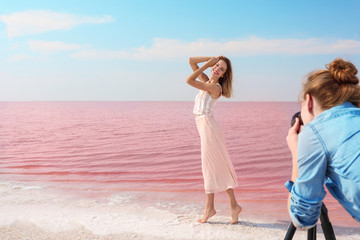 Female photographer taking pictures of model near pink lake