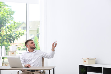Young man with air conditioner remote in office