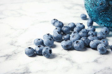 Fresh and juicy blueberries on marble table