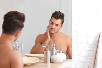 Young man with stubble ready for shaving near mirror in bathroom