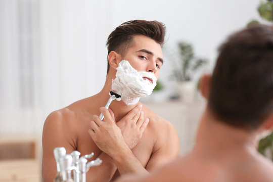 Young man shaving near mirror in bathroom