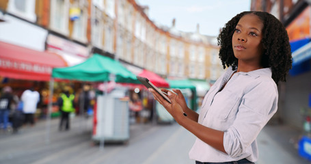 Attractive businesswoman at popular Brixton street market using tablet