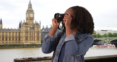 Portrait of black female standing by River Thames in London taking pictures
