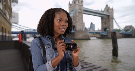 Attractive black woman takes photo of River Thames view of bridge in background