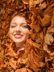 Beautiful young lady is lying between leaves.