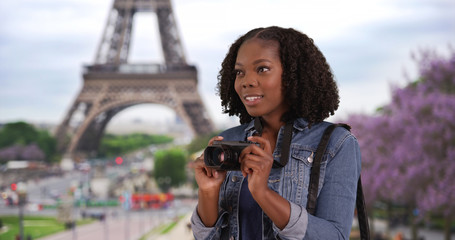 Pretty black female takes picture in Paris view of Eiffel Tower in background