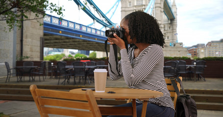Happy smiling female sits at outdoor cafe near Tower Bridge in London