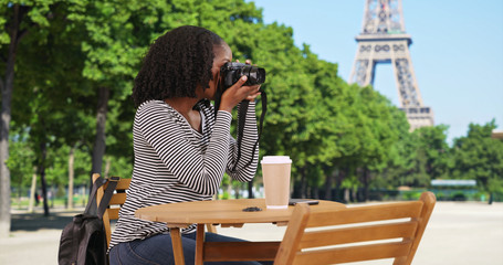 Happy smiling female sits at table near Eiffel Tower taking pictures with camera
