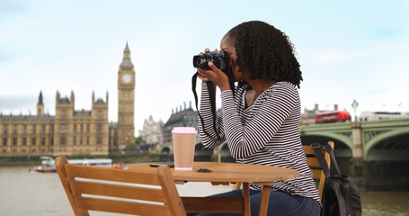 Smiling black female sits at table along River Thames taking photos with camera