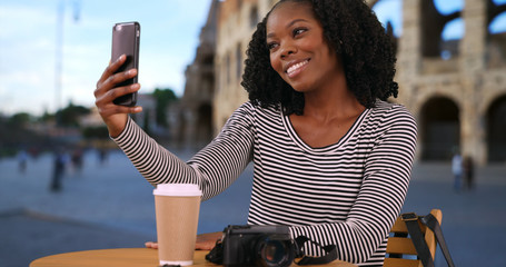 Pretty black woman takes a selfie with cellphone near Roman Coliseum in evening