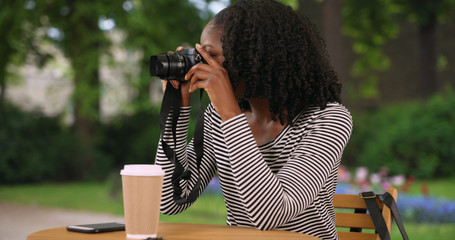 Cute black woman sits in lovely garden in Bruges taking pictures with camera