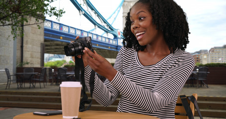 Black woman sits at outdoor cafe near Tower Bridge taking photos with camera