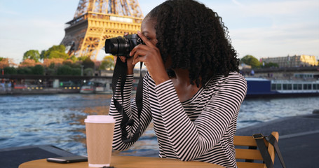 Attractive black woman sits at table along the Seine taking pictures with camera