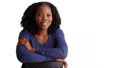 Smiling portrait of happy black woman sitting backwards in chair in studio