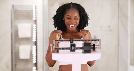 Beautiful black woman happily weighs herself on scale in bathroom