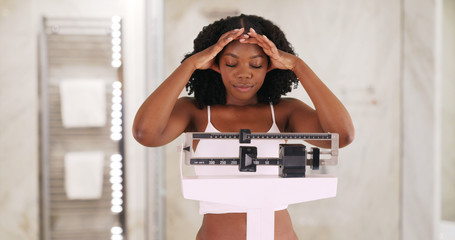 Young black woman weighs herself on scale, frowning and shaking her head