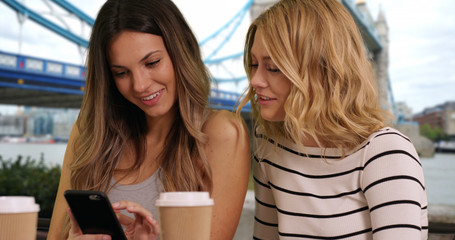 Close-up of two girls using smartphone at cafe near Tower Bridge in London