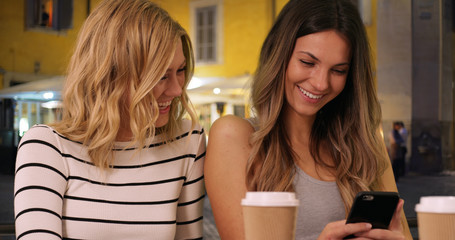 Close-up of two lovely girls using smart phone in cozy European town at night