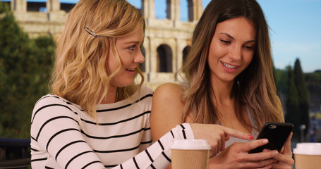 Couple of girls share pictures on phone in front of Colosseum in Rome