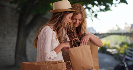 Good-looking women sitting with shopping bags talking on a public bench