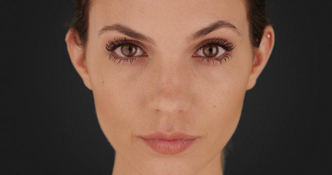 Portrait of pretty brunette gazing at camera on solid dark gray backdrop