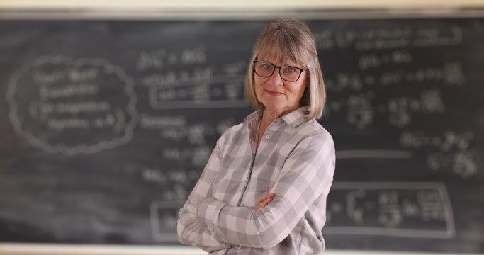 Confident senior woman teacher with arms crossed standing in front of chalkboard