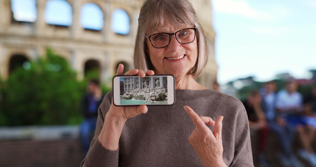 Joyful Caucasian old woman by Roman Colosseum showing video of Trevi Fountain