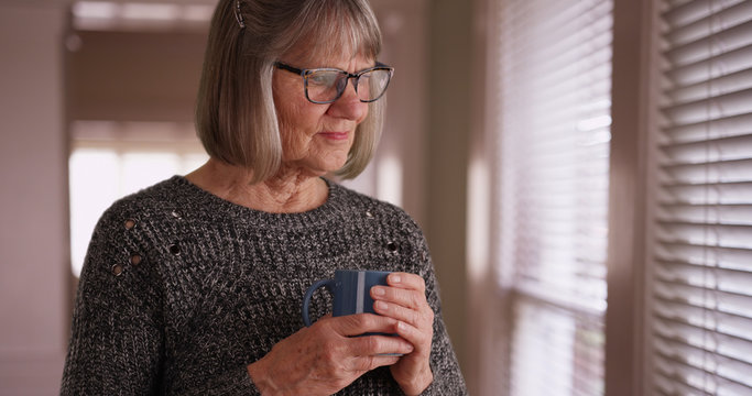 Somber old white woman contemplating and holding cup while looking out window