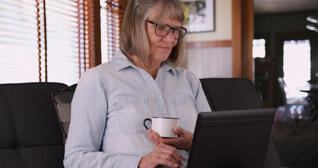 Retired aged white woman drinking tea while using laptop computer in living room