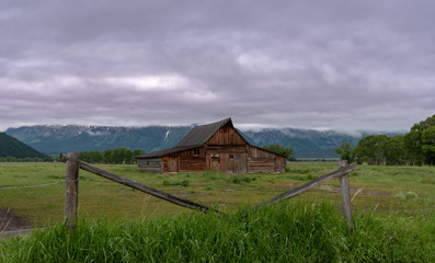 Barn Framed by Fence in front of mountains