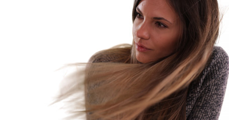 Beautiful woman with long brown hair blowing in the wind on white backdrop