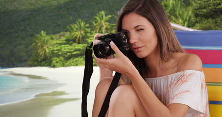 Woman taking photograph with camera sitting in beach chair in tropical setting