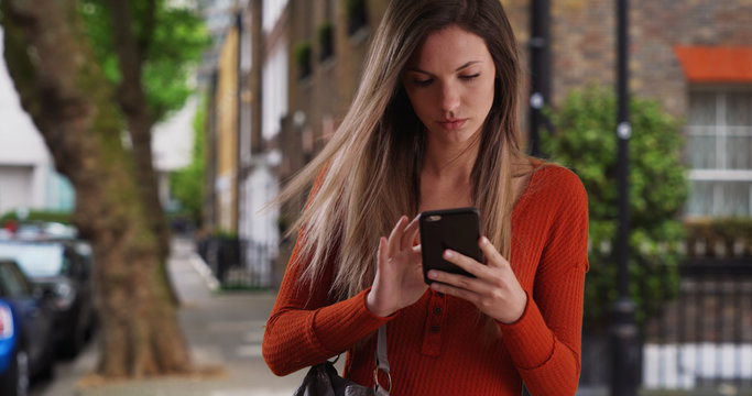 Young woman taking phone out of purse to send text while standing on sidewalk