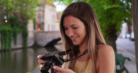 Happy Caucasian woman with camera taking photos while exploring city of Bruges