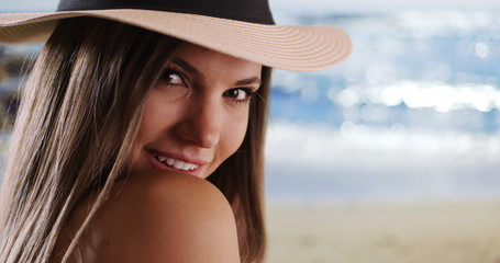 Close-up of woman wearing hat looking over her shoulder in sunny beach setting
