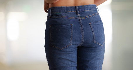 Close-up of millennial woman putting on blue jeans indoors private living area