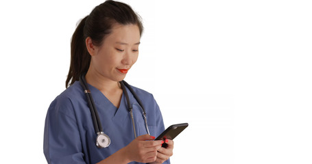 Happy young Asian doctor in scrubs texting with cell phone for copy space