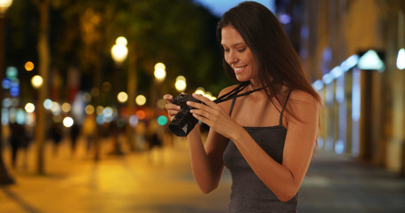 Traveling girl taking picture with dslr camera on the Champs-Elysees at night