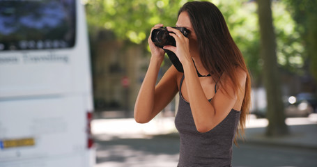 Pretty millennial tourist standing on street taking photo with dslr camera