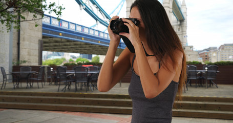 Pretty travel photographer in London England taking picture with dslr camera