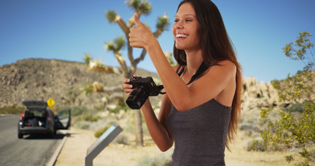 Pretty travel photographer in Joshua Tree taking picture with camera